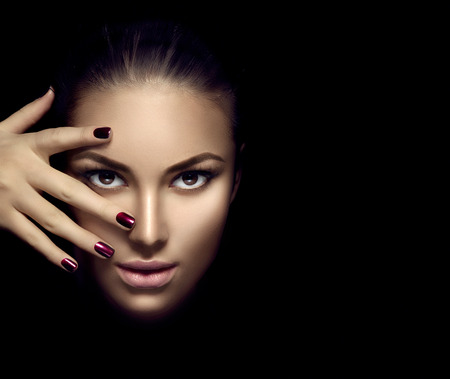 Modelka twarz dziewczyny, piękno kobiety makijaż i manicure na ciemnym tle