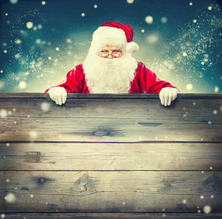 christmas gift: Happy Santa Claus holding wooden banner background. Christmas theme