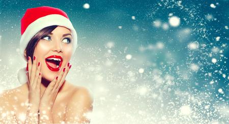 Kerstmis. Mooie verraste vrouw in de hoed van de Kerstman