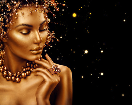 Beauty fashion model girl with golden skin, makeup and hairstyle isolated on black background Фото со стока