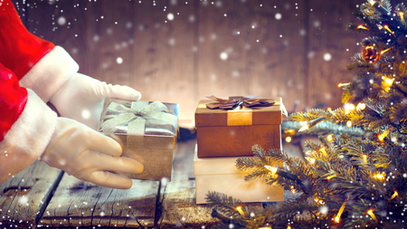 christmas gift: Santa Claus putting gift box under the Christmas tree with blinking garlands Stock Photo