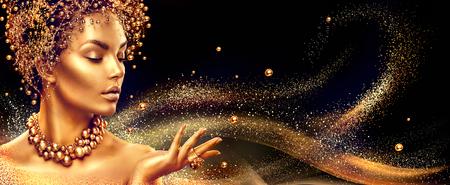 Золотая женщина. Красота моды модель девушка с золотой макияж, волосы и украшения на черном фоне