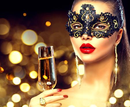 Mujer modelo atractiva con el vidrio de champán que llevaba máscara de la mascarada veneciana Foto de archivo - 66831650