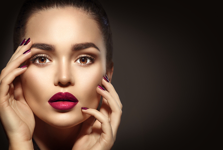red lip: Beauty brunette woman with perfect holiday makeup