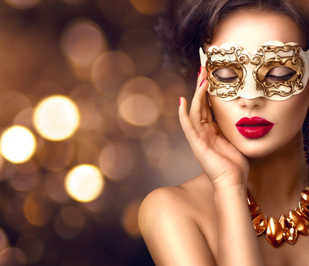 brown backgrounds: Beauty model woman wearing venetian masquerade carnival mask at party. Christmas and New Year celebration