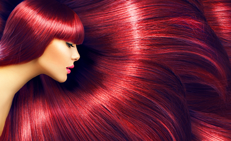Mooi haar. Brunette vrouw met lange rechte rode haren als achtergrond