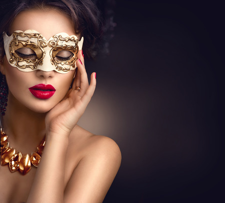 xmas background: Beauty model woman wearing venetian masquerade carnival mask at party. Christmas and New Year celebration