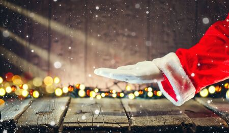 Christmas Santa Claus showing empty copy space on the open hand palm for text. Advertisement gesture presenting point