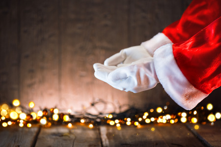 Christmas concept. Santa showing empty copy space on the open hands palms. Advertisement gesture presenting point
