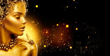 Golden vrouw. Schoonheid fashion model meisje met gouden make-up, haar en sieraden op zwarte achtergrond Stockfoto
