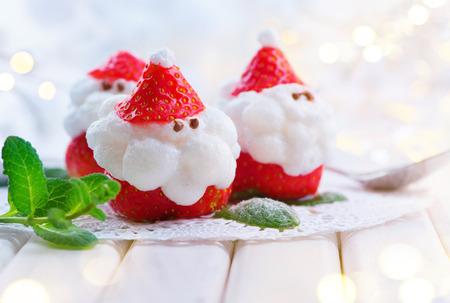 聖誕節聖誕老人草莓。滑稽的甜點塞滿了奶油。聖誕派對食物的想法