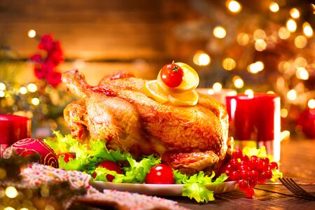 Christmas holiday family dinner. Decorated table with roasted turkey, Christmas tree