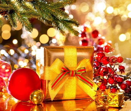 golden: Holiday Christmas scene. Gift box under the decorated Christmas tree