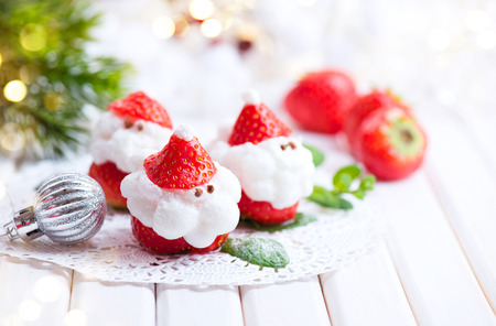 Christmas strawberry Santa. Funny dessert stuffed with whipped cream. Xmas party food idea Imagens