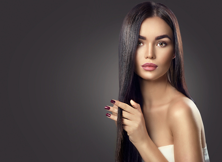 hand colored: Beauty brunette model girl touching long healthy hair