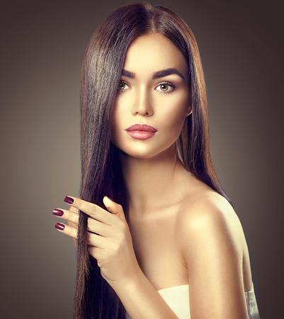 Belleza morena modelo de chica tocando el pelo sano marrón largo Foto de archivo