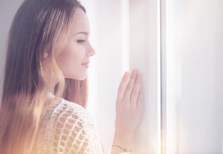 Jeune beauté femme romantique regardant par la fenêtre