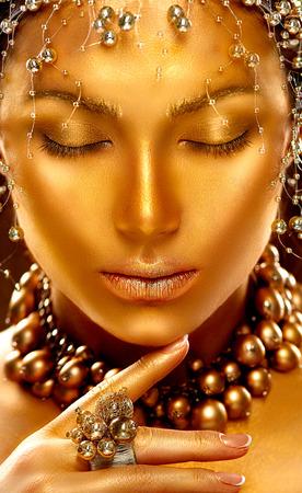 Beauty model girl with golden skin. Fashion art portrait Foto de archivo