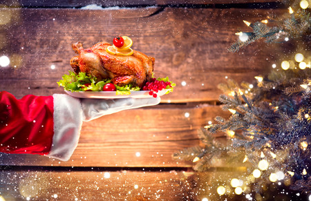 christmas gift: Christmas holiday dinner. Santas hand holding roasted chicken over wooden background