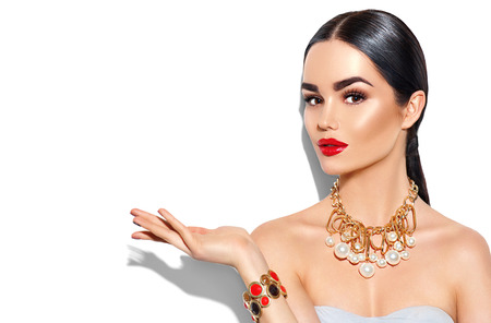Sexy young woman with perfect makeup and trendy golden accessories showing empty copy space on the open hand palm Stock Photo
