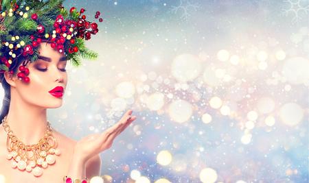 彼女の手に魔法の雪を吹くクリスマス冬のファッションの女の子