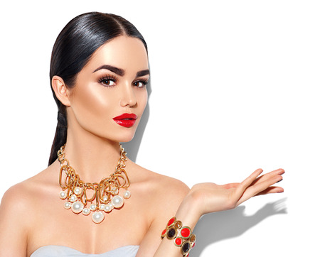 Sexy young woman with perfect makeup and trendy golden accessories showing empty copy space on the open hand palm Zdjęcie Seryjne