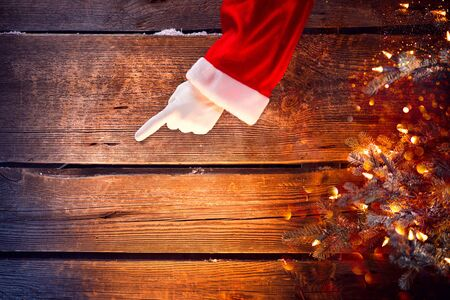 Christmas. Santa showing empty copy space on a wooden background
