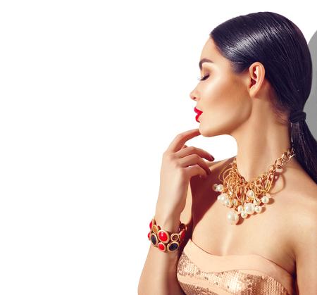 美容ファッションのブルネットのモデルの少女の肖像画。完璧なメイクとトレンディな黄金アクセサリーでセクシーな若い女性