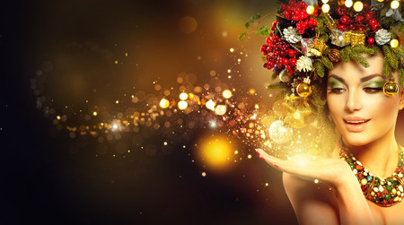 golden: Christmas magic. Beauty fashion model over holiday blurred background