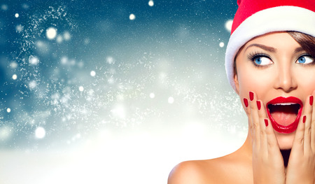 xmas background: Surprised Christmas girl. Beauty model woman in Santa Claus hat Stock Photo