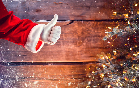 Santa Claus thumb up gesture over Christmas holiday wooden background