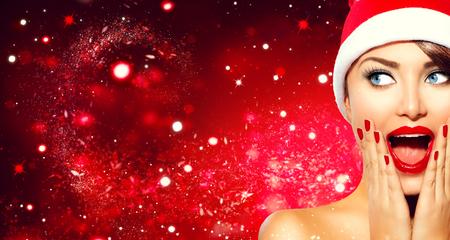 Surprised Christmas girl. Beauty model woman in Santas hat