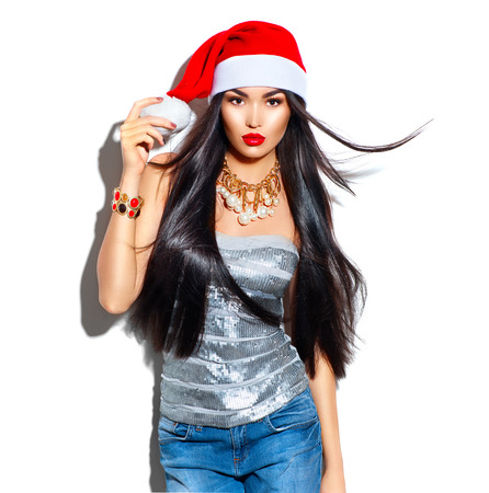 gold: Beauty Christmas fashion model girl with long straight flying hair in red santa hat