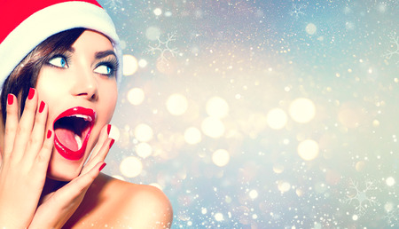 Surprised Christmas girl. Beauty model woman in Santas hat