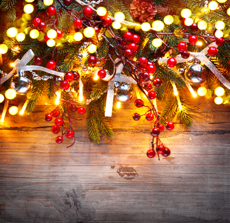 Christmas fir tree decorated with Christmas lights over wooden background