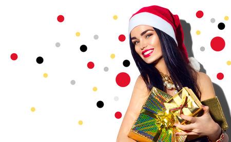 flying kiss: Christmas fashion model girl. Sexy Santa holding gifts Stock Photo