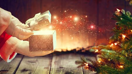 christmas gift: Santa Claus opens gift box over wooden background with Christmas tree