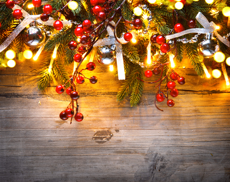 wood texture: Christmas fir tree decorated with Christmas lights over wooden background