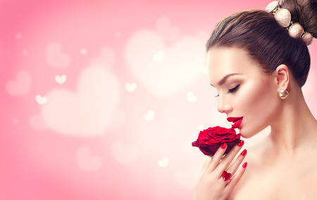 Valentines day. Woman with red rose. Fashion model girl face portrait Stok Fotoğraf