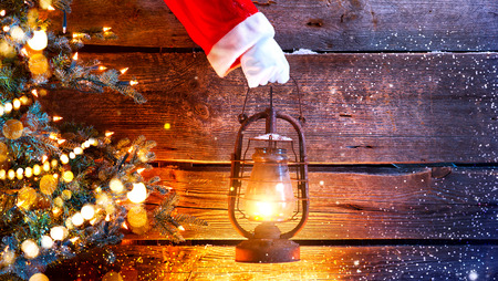 Kerst scène. Santa's hand die vintage olie lamp over houten achtergrond houdt Stockfoto