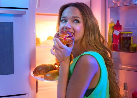 밤에 냉장고에서 음식을 복용하는 아름 다운 십 대 소녀의 초상화