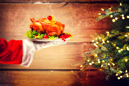 plate: Christmas holiday dinner. Santas hand holding roasted chicken over wooden background