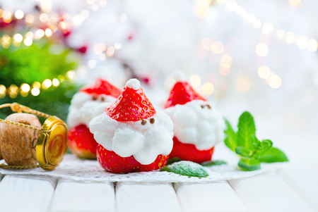 children party: Christmas strawberry Santa. Funny dessert stuffed with whipped cream. Xmas party food idea Stock Photo