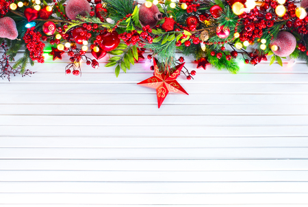 berry: Christmas and New Year decoration over white wooden background. Border art design with holiday baubles Stock Photo
