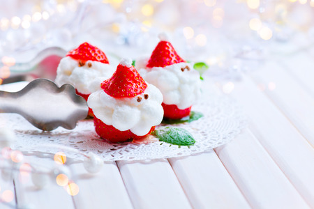 happy holidays: Christmas strawberry Santa. Funny dessert stuffed with whipped cream. Xmas party food idea Stock Photo