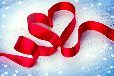 symbol: Valentines day. Red heart shaped satin ribbon over white wooden background Stock Photo