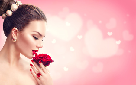 Valentines day. Woman with red rose. Fashion model girl face portrait Фото со стока