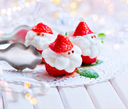 Christmas strawberry Santa. Funny dessert stuffed with whipped cream. Xmas party food idea Stock Photo
