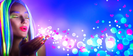 hand: Valentines day. Beauty girl on disco party in neon light, blowing Valentine neon hearts