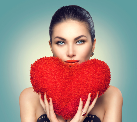 s day: Valentines day. Sexy model girl with heart shaped fluffy red pillow Stock Photo